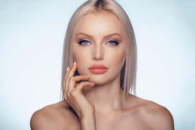 Chiuda sul ritratto di bellezza di una donna bionda con pelle perfetta e labbra carnose