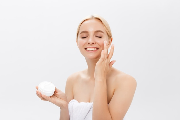 Chiuda sul ritratto di bellezza di una donna mezzo nuda bella di risata che applica la crema di fronte