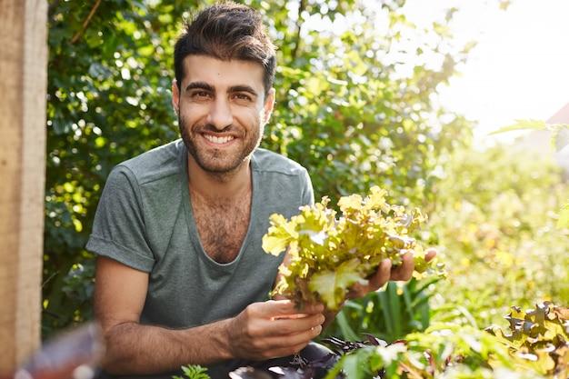 Chiuda sul ritratto di bello contadino caucasico barbuto dalla carnagione scura sorridente, lavorando in giardino, raccoglie foglie di lattuga, preparandosi per l'incontro serale con gli amici nella sua casa