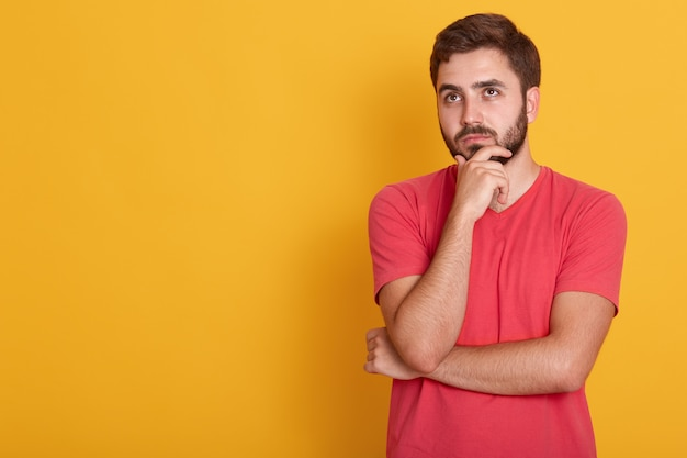 Chiuda sul ritratto di forte ragazzo sicuro che tiene la sua mano sotto il mento, colpo dello studio, fammi pensare, il maschio indossa la maglietta casuale rossa