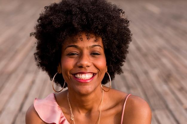 Chiuda sul ritratto di giovane bella donna afroamericana felice che si siede sul pavimento e sul sorridere di legno. stagione primaverile o estiva. casuale