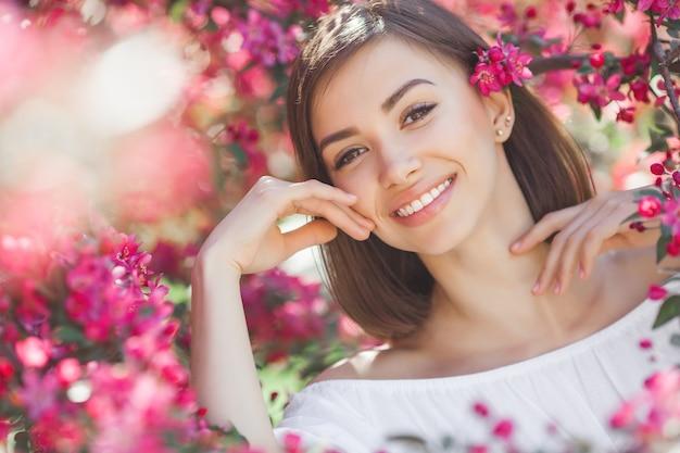 Chiuda sul ritratto di giovane bella donna con pelle liscia perfetta. signora attraente in fiori. ritratto facciale di bella femmina.