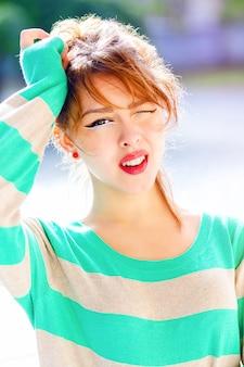 Chiuda sul ritratto di giovane bella ragazza avere emozioni potenti, sorpreso e scioccato, divertirsi, indossare un maglione luminoso e truccarsi.