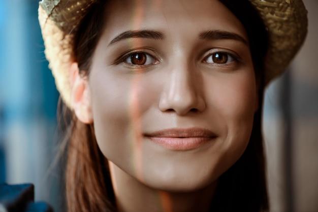 Chiuda sul ritratto di giovane bello sorridere della ragazza del brunette.