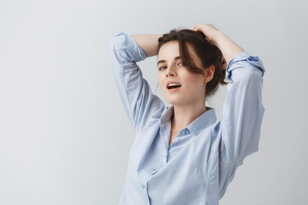 Chiuda sul ritratto di giovane donna che si fa l'acconciatura con l'espressione felice e allegra.