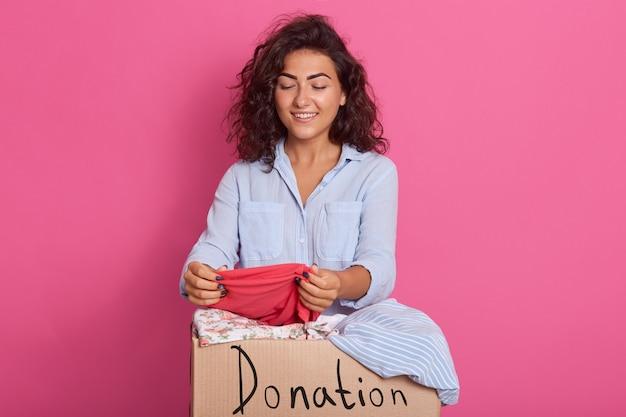 Chiuda sul ritratto di giovane donna con capelli ondulati scuri, posando vicino alla scatola di donazione dei vestiti, controllando il rosa