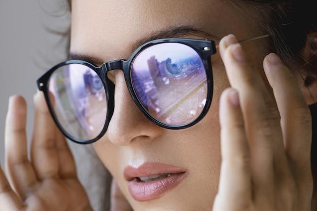 Chiuda sul ritratto di giovane donna con una riflessione della città moderna dentro gli occhiali