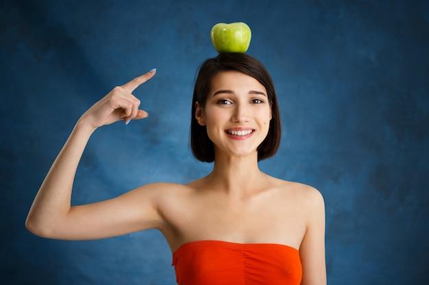 Chiuda sul ritratto di giovane donna tenera che indica con il dito alla mela sulla sua testa sopra la parete blu