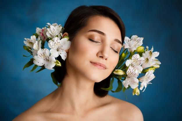 Chiuda sul ritratto di giovane donna tenera con i fiori bianchi sopra la parete blu