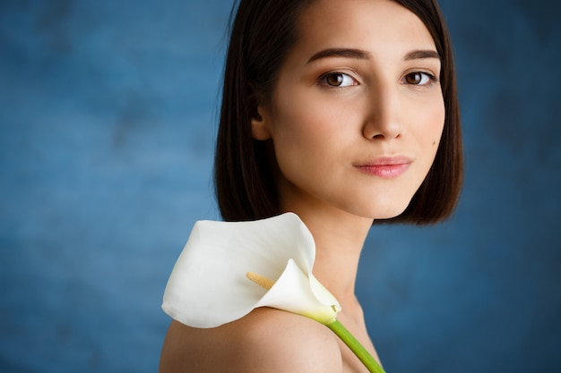 Chiuda sul ritratto di giovane donna tenera con il fiore bianco sopra la parete blu