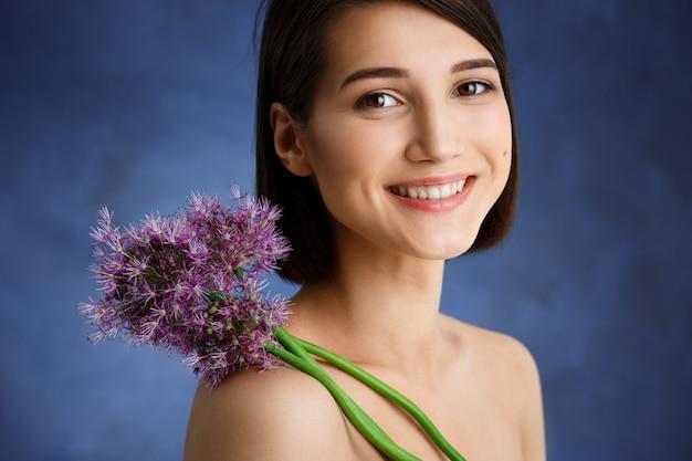 Chiuda sul ritratto di giovane donna tenera con il fiore lilla sopra la parete blu