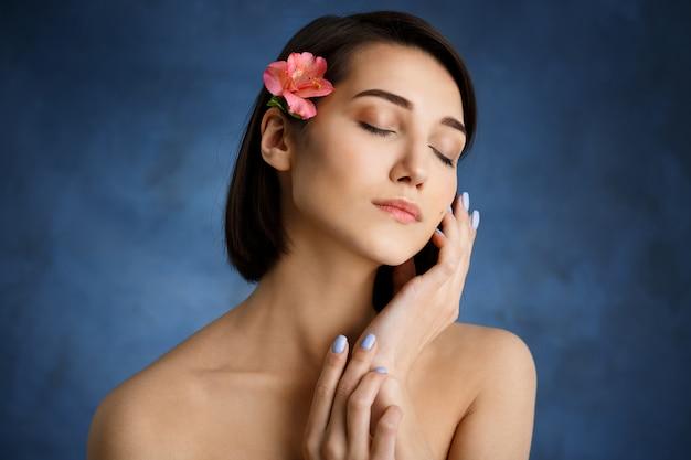 Chiuda sul ritratto di giovane donna tenera con il fiore rosa in capelli sopra la parete blu