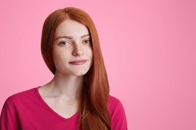 Chiuda sul ritratto di giovane femmina lentigginosa indossa un maglione rosa casual, guarda con fiducia la fotocamera, sogna di qualcosa