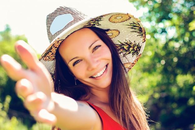Chiuda sul ritratto di giovane ragazza sorridente con cappello di paglia