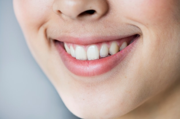 Chiuda sul ritratto di giovane sorridere asiatico dei denti della ragazza