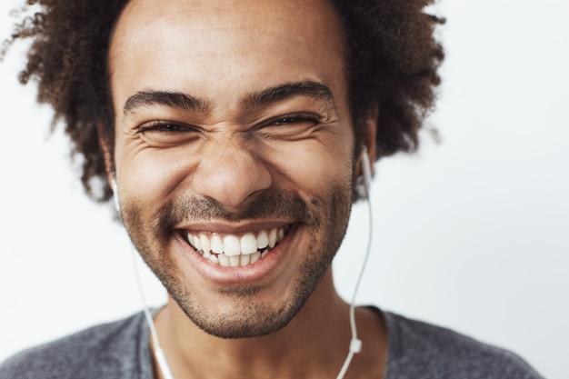 Chiuda sul ritratto di giovane uomo africano felice che sorride ascoltando la risata ottimistica di musica in streaming. concetto di gioventù.