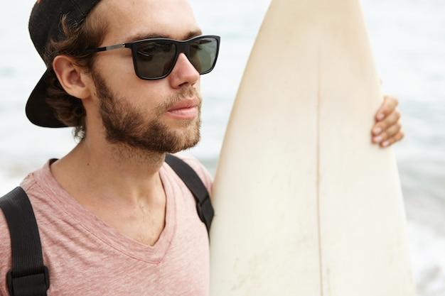 Chiuda sul ritratto di giovane uomo barbuto bello in occhiali da sole alla moda che posano all'aperto con la sua tavola da surf bianca, godendo di bello paesaggio marino