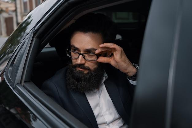 Chiuda sul ritratto di giovane uomo d'affari attraente in un'automobile