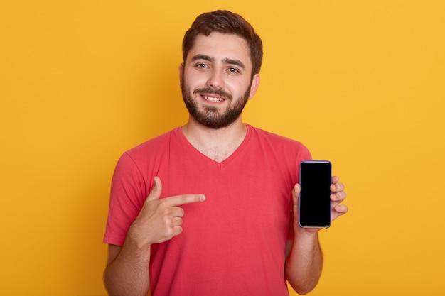 Chiuda sul ritratto di giovane uomo felice in camicia rossa che mostra lo schermo in bianco nero dello smart phone
