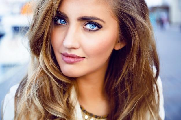 Chiuda sul ritratto di moda di donna sexy seducente con grandi occhi azzurri, labbra carnose, pelle perfetta e acconciatura arricciata lunga e soffice. trucco naturale.