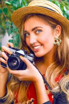 Chiuda sul ritratto di moda di giovane donna abbastanza bionda con trucco naturale, indossando il cappello di paglia, tenendo la vecchia macchina fotografica d'epoca retrò hipster. all'aperto.