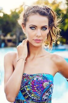 Chiuda sul ritratto di moda di giovane donna splendida sexy al sole con labbra carnose di pelle abbronzata perfetta e grandi occhi con lenti colorate. indossare abiti luminosi e ghirlande di diamanti. atmosfera estiva.