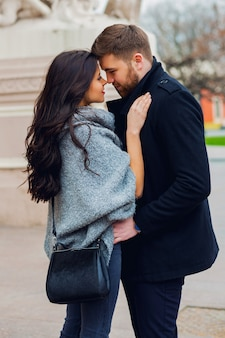 Chiuda sul ritratto di moda di giovane ragazza alla moda glamour e ragazzo innamorato. coppia camminare per strada in autunno soleggiato. caldi colori autunnali. indossa un vestito nero alla moda.