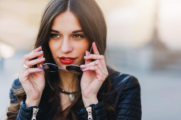 Chiuda sul ritratto di modo della giovane donna abbastanza seducente con gli occhiali da sole, posare all'aperto. labbra rosse, acconciatura ondulata.