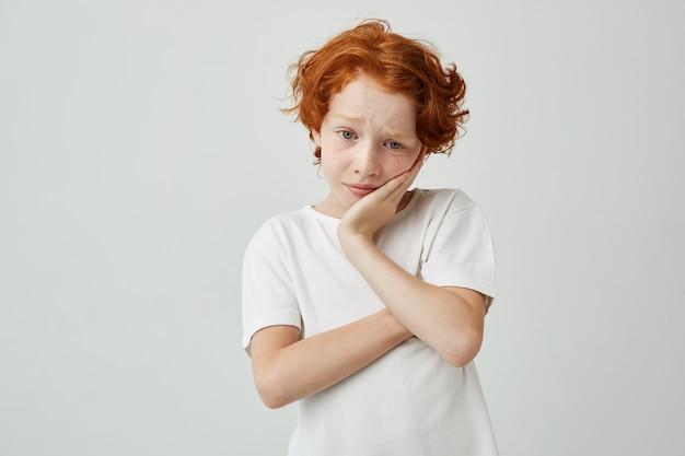 Chiuda sul ritratto di piccola testa della tenuta del ragazzo dello zenzero con la mano che guarda da parte con l'espressione triste