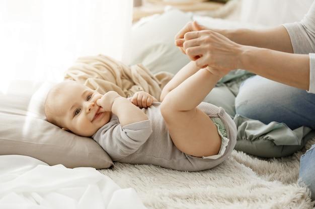 Chiuda sul ritratto di piccolo figlio neonato che si trova sul letto, mentre gioca con la madre. ragazzo sorridente e metti le dita in bocca cercando felice e spensierato.