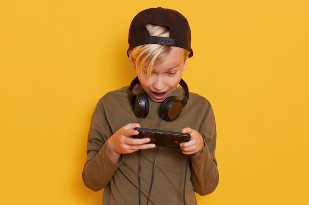 Chiuda sul ritratto di piccolo ragazzo biondo che posa con il telefono cellulare a disposizione isolato sopra giallo