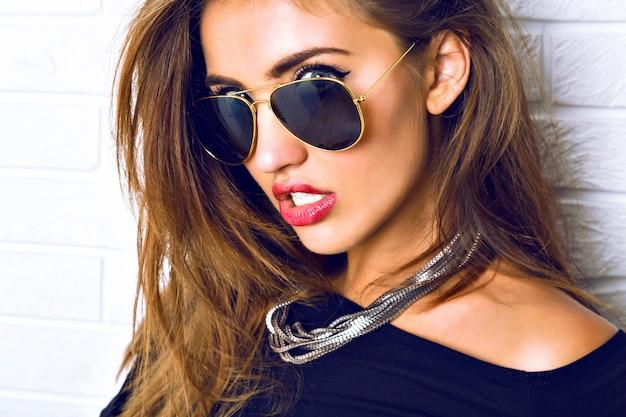 Chiuda sul ritratto di splendida donna bruna sexy, gioielli di lusso, occhiali da sole vintage, stile urbano. trucco luminoso dei capelli lunghi.