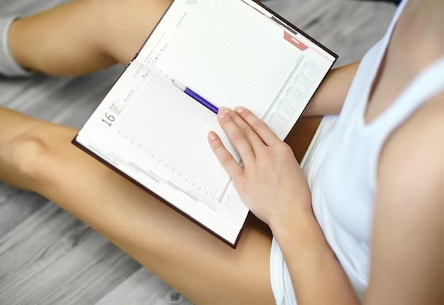 Chiuda sul ritratto di stile di vita della giovane donna che si siede sul pavimento e che fa le note al suo diario