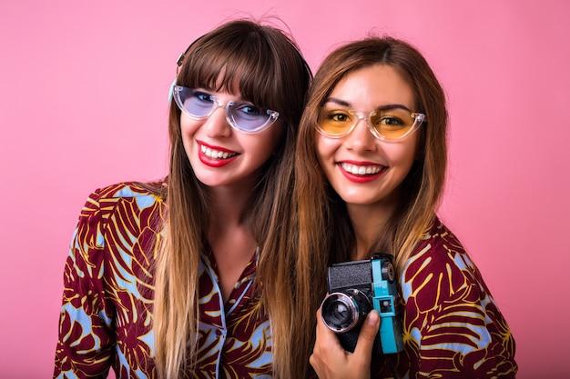 Chiuda sul ritratto di stile di vita dello studio di due amici graziosi che indossano abiti abbinati stampati e occhiali da sole, tenendo la fotocamera vintage