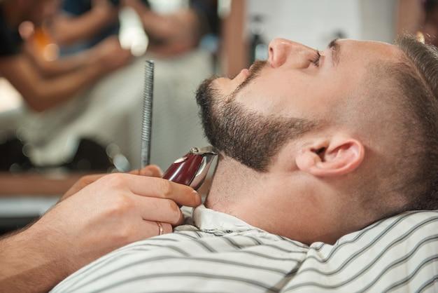 Chiuda sul ritratto di un bel giovane barbuto che ottiene la sua barba rifilata da un barbiere professionista.