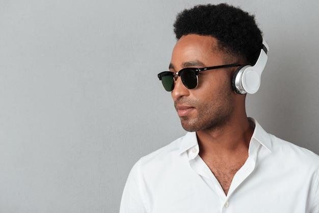 Chiuda sul ritratto di un giovane uomo africano in occhiali da sole