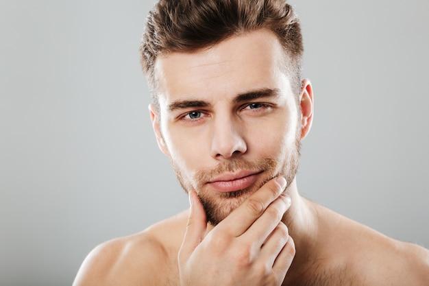 Chiuda sul ritratto di un giovane uomo barbuto che guarda l'obbiettivo