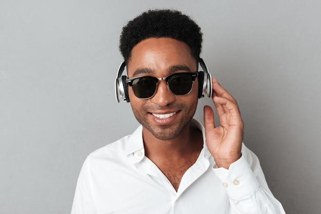 Chiuda sul ritratto di un uomo africano felice in occhiali da sole
