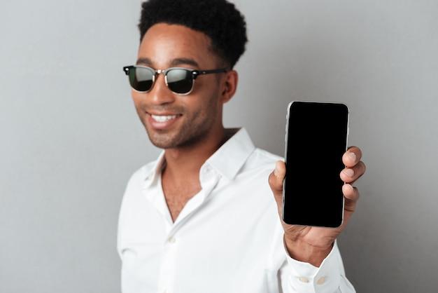 Chiuda sul ritratto di un uomo africano sorridente felice in occhiali da sole