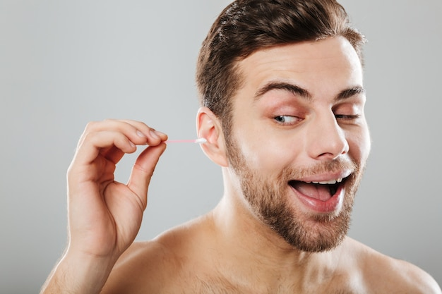 Chiuda sul ritratto di un uomo allegro che pulisce le sue orecchie