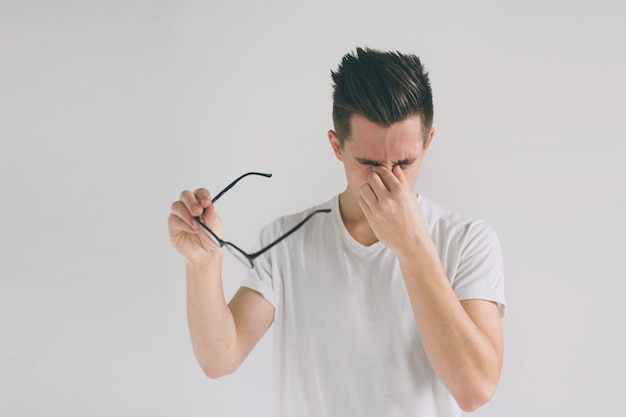 Chiuda sul ritratto di un uomo attraente con gli occhiali. il povero ragazzo ha problemi di vista. si stropiccia il naso e gli occhi a causa della stanchezza. chiuda sul ritratto di un uomo divertente con gli occhiali. noi