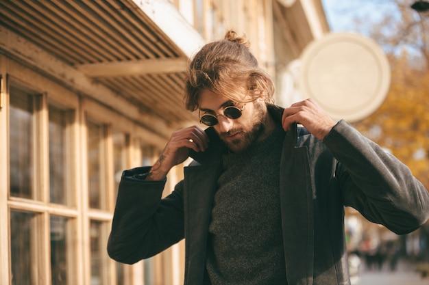 Chiuda sul ritratto di un uomo barbuto alla moda che indossa gli occhiali da sole