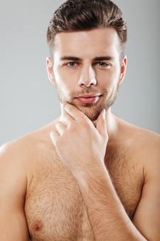 Chiuda sul ritratto di un uomo barbuto mezzo nudo sorridente
