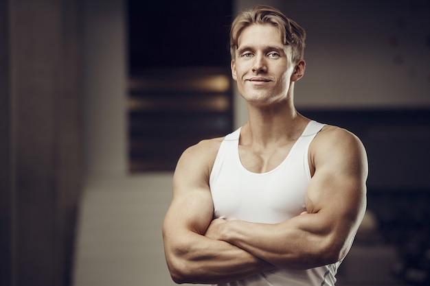 Chiuda sul ritratto di un uomo bello di forma fisica in camicia bianca in palestra