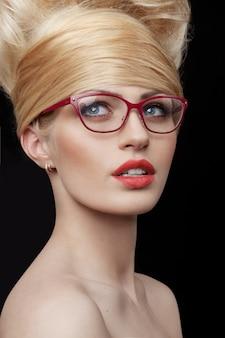 Chiuda sul ritratto di una bella ragazza bionda che indossa occhiali da vista