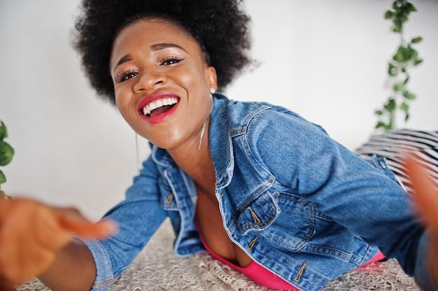 Chiuda sul ritratto di una donna afroamericana attraente con il rivestimento dei jeans di usura dei capelli di afro, posato alla stanza bianca. modello nero alla moda.
