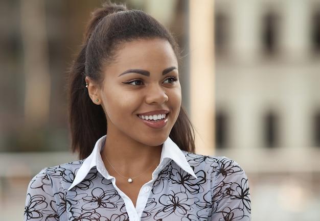 Chiuda sul ritratto di una donna afroamericana che sorride con il tramonto
