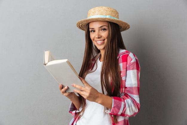 Chiuda sul ritratto di una donna felice sorridente in cappello di paglia che tiene un libro,