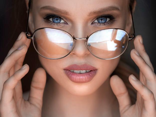 Chiuda sul ritratto di una donna in occhiali.