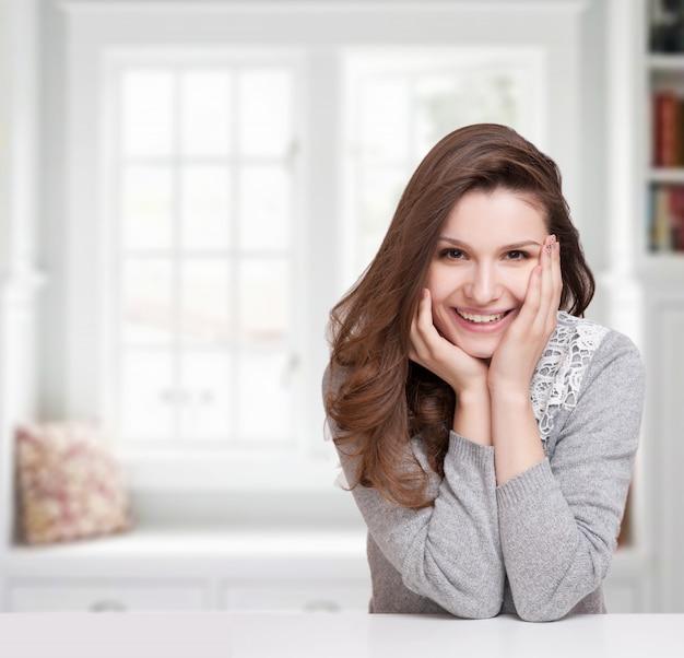 Chiuda sul ritratto di una donna sorridente felice che riposa il suo mento sulle sue mani e che esamina direttamente la macchina fotografica